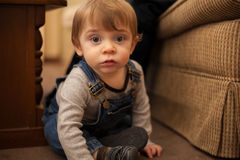 Lustiges Kleinkind, das auf dem Boden sitzt Lizenzfreies Stockbild