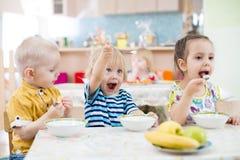 Lustiges Kleinkind, das im Kindergarten spielt und isst stockfoto
