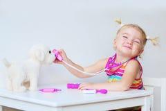 Lustiges Kleinkind, das zuhause Doktor spielt Stockbilder