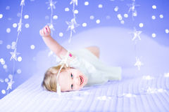 Lustiges Kleinkindmädchen in einem weißen Kleid zwischen Weihnachtslichtern Stockfotografie