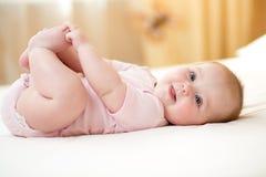 Lustiges lächelndes Babysäuglingsmädchen, das mit ihren Füßen spielt Stockbild