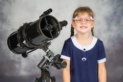 Lustiges lächelndes bereitstehendes Teleskop des Mädchenbebrillten Amateurastronomen Stockbild