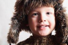 Lustiges lächelndes Kind in einem Pelzhut. Modekind. Winterart. kleiner Junge. Kinder Stockfoto