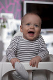 Lustiges lächelndes Kind im Babystuhl Lizenzfreie Stockfotos