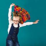 Lustiges lächelndes kleines Mädchen mit dem großen Rucksack, der f springt und hat Stockfotografie