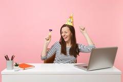 Lustiges Mädchen mit geschlossenen Augen im Geburtstagsfeierhut mit dem Spielen des Rohrtanzens genießen zu feiern, während Arbei stockfotos