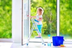 Lustiges Mädchen, das ein Fenster im Reinraum wäscht Lizenzfreie Stockfotografie