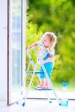 Lustiges Mädchen, das ein Fenster wäscht Stockfotografie