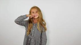 Lustiges Mädchen, das am eingebildeten Handy auf weißem Hintergrund plaudert stock video footage