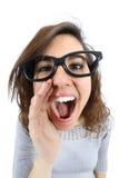 Lustiges Mädchen, das mit ihrer Hand an ihrem Mund schreit und nennt Stockfotos