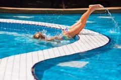 Lustiges Mädchen, das unter Wasser im Swimmingpool taucht stockfoto