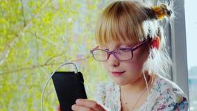 Lustiges Mädchen in den Kopfhörern hörend Musik, entlang singend Sitzt auf dem Fensterbrett gegen das Fenster, außerhalb stock footage