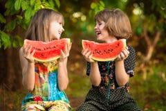 Lustiges Mädchen der kleinen Schwestern isst Wassermelone im Sommer stockfotos