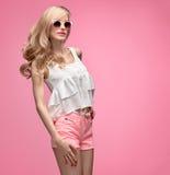 Lustiges Mädchen der Mode, das Spaß hat Modische rosa kurze Hosen Stockbilder