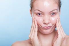 Lustiges Mädchen des Porträts in Gesichts ziehen weg Maske ab. Schönheitshautpflege. Stockbild