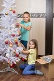 Lustiges Mädchen entfernen Weihnachtsdekorationen mit Weihnachtsbaum Lizenzfreie Stockbilder
