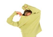 Lustiges Mädchen entfernt eine grüne Strickjacke Lizenzfreie Stockfotos