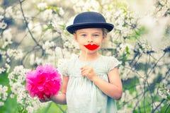 Lustiges Mädchen im Hut und mit den gefälschten Lippen arbeiten im Frühjahr im Garten Stockfotografie