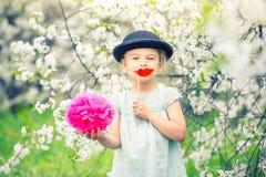Lustiges Mädchen im Hut und mit den gefälschten Lippen arbeiten im Frühjahr im Garten Lizenzfreie Stockbilder