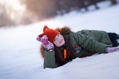 Lustiges Mädchen im Winterfoto Weiße Schneeflocken auf einem blauen Hintergrund lizenzfreies stockfoto