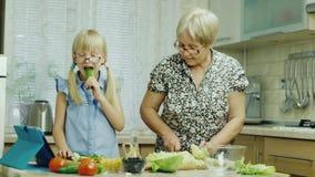 Lustiges Mädchen 6 Jahre alte Hilfen ihre Großmutter bereiten Mahlzeiten in der Küche vor Isst eine Gurke, hat Spaß zusammen Gesu stock video
