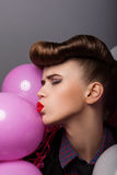 Lustiges Mädchen mit bunten Luft-Ballonen Gesicht verziehendes Stockfotos