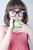 Lustiges Mädchen mit der Herdensonnenbrille, die einen Ballon durchbrennt Stockbild