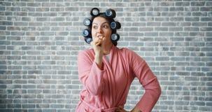Lustiges Mädchen mit Haarlockenwicklern singend in der Haarbürste und tanzend, Spaß habend stock video footage