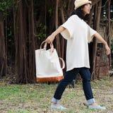 Lustiges Mädchen mit Handtasche auf Naturhintergrund lizenzfreie stockfotografie