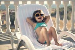 Lustiges Mädchen nimmt auf einem Sonnenruhesessel ein Sonnenbad stockfoto