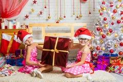 Lustiges Mädchen zwei, das ein großes Geschenk sitzt auf einer Wolldecke hält Stockfotos