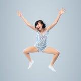 Lustiges Mädchen in den Pyjamas, die für Freude springen Stockbild