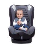 Lustiges nettes Baby, das in einem Autositz, lokalisiert sitzt Stockfoto