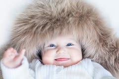 Lustiges nettes Baby, das enormen Winterhut trägt Stockfoto