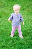 Lustiges nettes Baby mit Blume auf einer Wiese Stockbilder