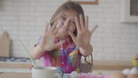 Lustiges nettes emotionales kleines M?dchen des Portr?ts, das H?nde in der blauen Farbe, Grimassen machend zur Kamera in der K?ch stock video footage