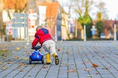 Lustiges nettes Kind in der roten Jacke, die blaues Spielzeugauto fährt und f hat Lizenzfreies Stockfoto