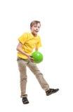 Lustiges nettes Kind im gelben T-Shirt, das mit einem Ball springt Stockfotografie