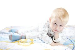 Lustiges nettes kleines Kind in den Pyjamas mit dem blonden Haar liegt auf einem Bett Stockbild