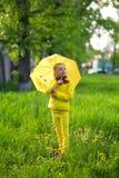 Lustiges nettes Mädchen, das den gelben Mantel hält den bunten Regenschirm spielt im Garten durch Regen- und Sonnenwetter auf ein lizenzfreie stockbilder