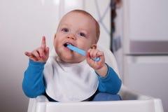 Lustiges neunmonatiges Baby in einem Baby chairmouth Stockfotografie