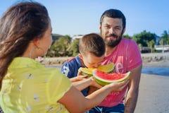 Lustiges Picknick der schönen glücklichen Familie auf Sandwüstestrand Stockfotos