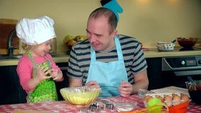 Lustiges Porträt der netten kleinen Tochter mit dem hübschen Vater, der mit Mehl spielt stock footage