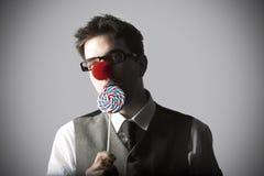 Lustiges Porträt des jungen stilvollen Mannes mit Clownnasenessen lolli Stockbild