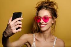 Lustiges Porträt eines lächelnden jungen Mädchens in den rosa Gläsern, das selfie am Telefon auf gelbem Hintergrund macht lizenzfreies stockfoto
