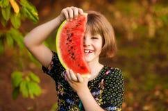 Lustiges Portr?t des unglaublich sch?nen kleinen M?dchens, das Wassermelone, gesunden Fruchtimbi? isst stockbilder