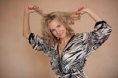 Lustiges Portrait eines Mädchens, das mit dem Haar spielt Stockbild