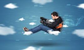 Lustiges racedriver junger Mann, der zwischen Wolkenkonzept fährt Stockbilder
