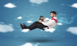 Lustiges racedriver junger Mann, der zwischen Wolkenkonzept fährt Lizenzfreie Stockfotografie