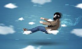 Lustiges racedriver junger Mann, der zwischen Wolkenkonzept fährt Lizenzfreie Stockbilder